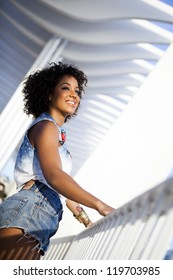 Portrait of a young black woman, fashion model wearing short jeans with afro hairstyle in urban background