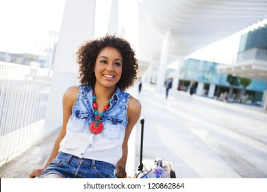 Portrait of a young black woman, fashion model wearing short jeans with afro hairstyle in train station