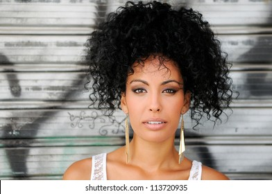 Portrait of a young black woman, model of fashion in urban background, with afro hairstyle