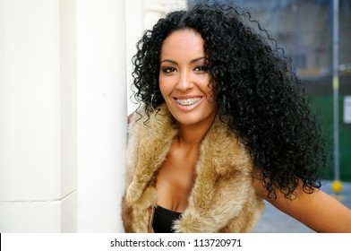 Portrait of a young black woman, model of fashion, wearing fur vest, with braces and afro hairstyle in urban background
