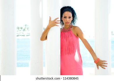 Portrait of a young black woman, model of fashion, with pink dress and earrings. Afro hairstyle