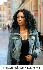 Portrait of a young black woman, model of fashion in urban background with denim jacket