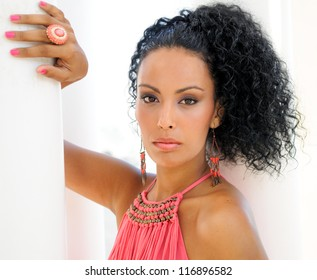 Portrait of a young black woman, model of fashion, with pink dress and earrings, with afro hairstyle