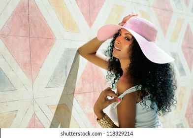 Portrait of a young black woman, model of fashion wearing dress and sun hat, with afro hairstyle in urban background