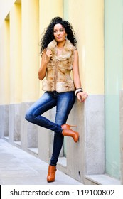 Portrait of a young black woman, model of fashion wearing fur vest and jeans