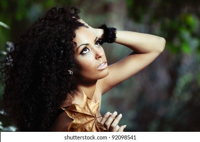 Portrait of a young black woman in the park with a dry leaf