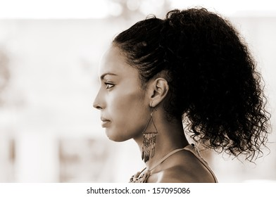 Portrait of a young black woman profile, model of fashion, with pink dress and earrings. Afro hairstyle
