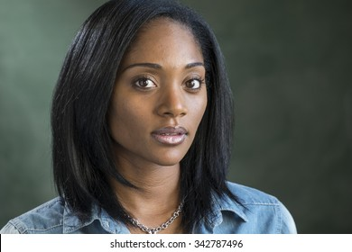 Portrait of a young black woman staring at the camera, no expression,
