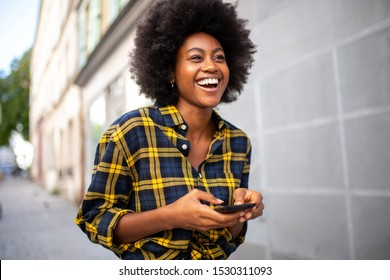Portrait of young black woman walking on street holding mobile phone