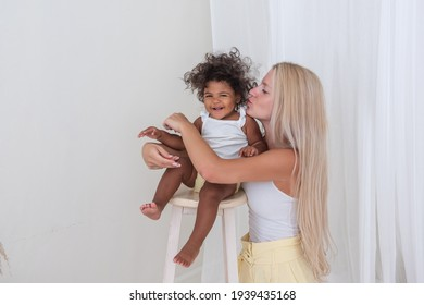 Portrait of young blond Caucasian mother and African American happy curly daughter on white background. A girl stands on a wooden chair, a woman hugs, kisses a baby. Adoption, mixed ethnic family.