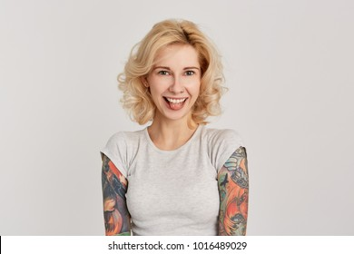 Portrait of young blond girl with tattooed arms, pierced nose and wearing white casual t-shirt smiling and showing her tongue. Funny. Isolated on white wall.