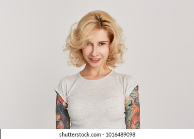Portrait of young blond girl with tattooed arms, pierced nose and wearing white casual t-shirt looking into the camera sullenly and sarcastic smile. Isolated on white wall.