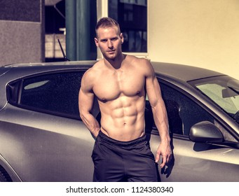 Portrait of young blond handsome muscular topless man leaning on car