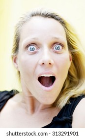Portrait of a young blond woman with big blue eyes looking surprised, shocked.