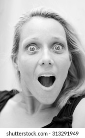 Portrait of a young blond woman with big blue eyes looking surprised, shocked in black and white.