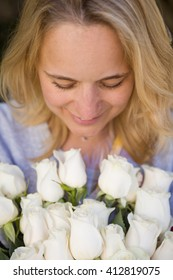 Portrait of young blond woman with big bunch of white roses. Girl with bouquet of flowers. Present for woman.