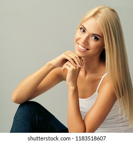 Portrait of young blond woman in fitness wear, sitting on floor, against grey wall.