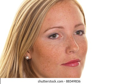 portrait of a young blond woman with freckles on a white background