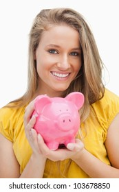 Portrait of a young blond woman holding a piggy-bank against white background