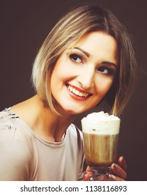 Portrait of young blond woman holding cafe latte cup