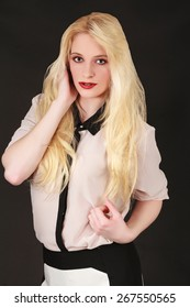 Portrait of a young blond woman with long hair, red lipstick, fashionably dressed on black background. / Portrait of a young blond woman with long hair