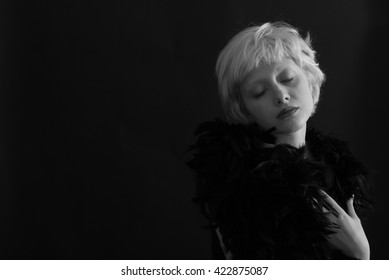 Portrait of young blond woman posing with feathers on black background -  Black and White Photography