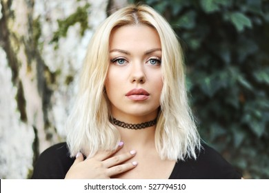portrait of young blond woman posing outdoor looking at camera