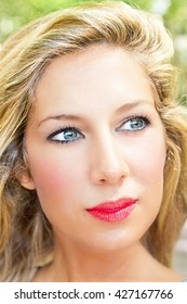 Portrait of a young blond woman with red lips