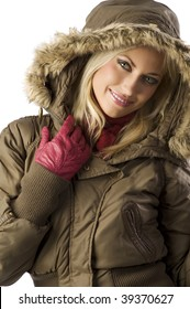 portrait of a young blond woman in winter jacket with hood and fur smiling in camera