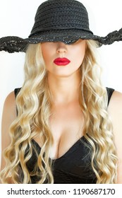 Portrait of a young blonde in a black hat with Decollete, on white background. Close-up. Bright red lips.