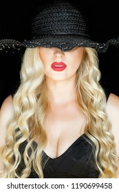 Portrait of a young blonde in a black hat with a decollete, over a black background. Close-up. Bright red lips.