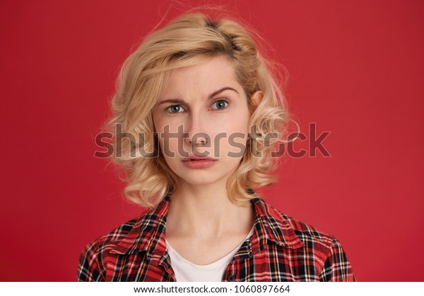 Portrait of young blonde female wears checkered red  shirt, feels doubt and surprised. Negative emotions. Facial expression. Isolated over red background