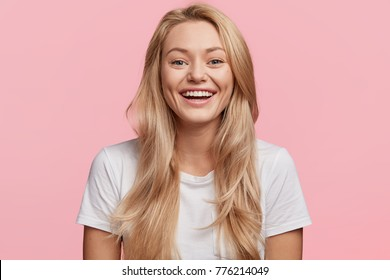 Portrait of young blonde positive female with cheerful expression, dressed in casual white t shirt, rejoices to recieve good job offer, isolated over pink background. Beautiful woman indoor.