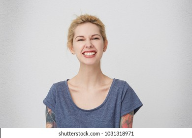 Portrait of young blonde  stylish girl with tattoos smiling and feels happy, keeps teeth clenched. Isolated over white wall