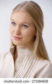 Portrait of young blonde woman with blue eyes, looking away, daydreaming.
