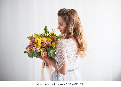 Portrait of a young blonde woman with bouquet. Woman's face with make-up and hairstyle.