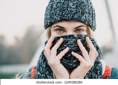 portrait of young blonde woman closing face with winter scarf. Beuatiful eyes, winter concept