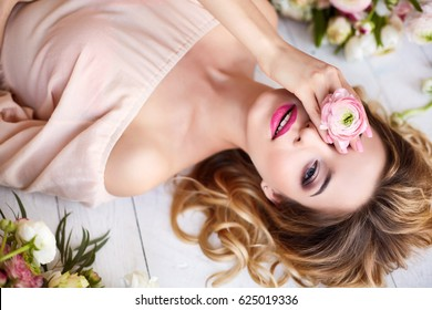 Portrait of a young blonde woman in flowers. Woman's face with make-up and hairstyle