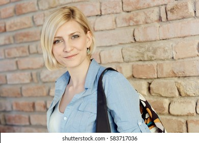 Portrait of young blonde woman front of brick wall.