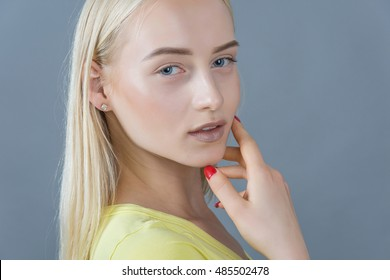 portrait of young blonde woman gray background studio