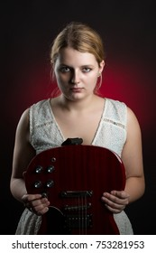 Portrait of a young blonde woman holding a electric guitar