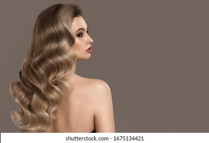 Portrait of young blonde woman. Long beautiful wavy hair.