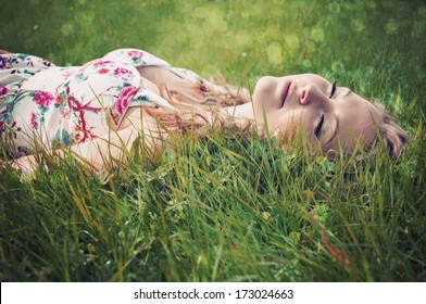 Portrait of a young blonde woman lying on grass with eyes shut.