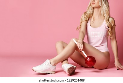 Portrait of young blonde woman sitting in sexy body vest hold huge sweet lollypop on pastel color pink background