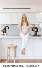 Portrait of a young blonde woman sitting on her kitchen benchtop at home