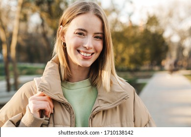 Portrait of young blonde woman wearing jacket smiling and looking at camera while walking in park