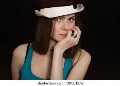 portrait of young blue-eyed girl in white hat on black background