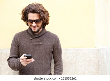 """Portrait of a young bohemian man using his """"smart phone"""" while leaning on a yellow wall, smiling outdoors."""