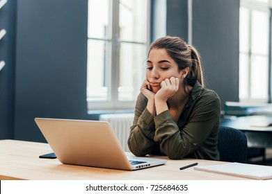 Portrait of young bored attractive female student looking at laptop.