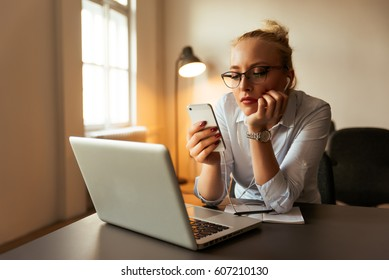 Portrait of young bored attractive woman at office desk, with laptop, looking for some good music